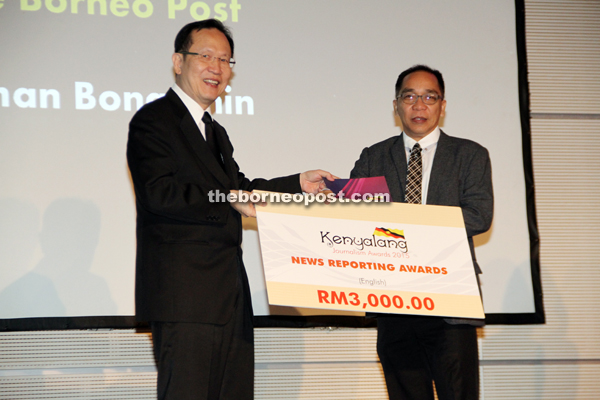 Peter accepts the mock cheque from Dato Henry Lau (left).