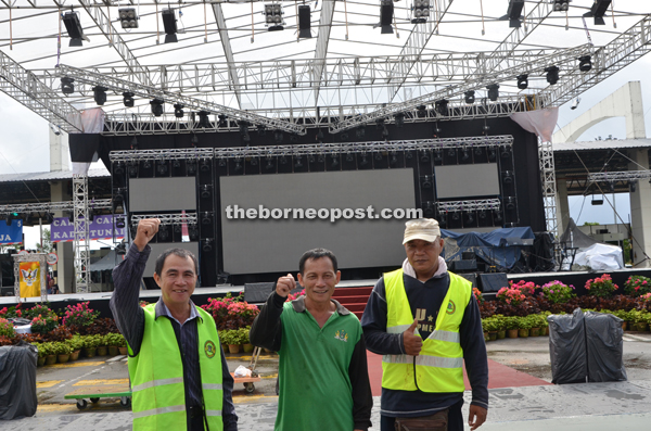 Kuching North City Commission (DBKU) workers (from left) Salleh Bol, Lajep Juan and Ariffin Sabu give their thumbs-up to the abolishment of the bridge toll.