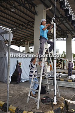 A worker installing light for the centre stage at the Toll Plaza.