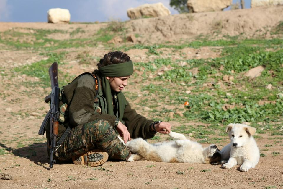"Syriac Christian Lucia, member of the battalion called the ""Female Protection Forces of the Land Between the Two Rivers"" plays with puppies during training on December 1, 2015 at their camp in the town of al-Qahtaniyah. -AFP Photo."