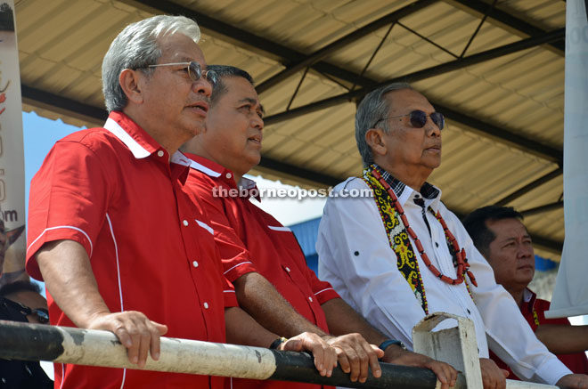(From right) Adenan, Aaron and Masing watching the 30-horsepower powerboat race.