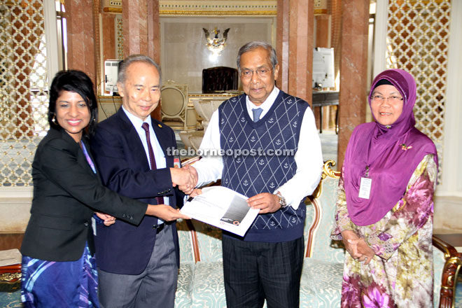 Simon (second left) presenting a memorandum to Adenan, witnessed by Gabriel (left) and Sutinah (right). — Photo by Chimon Upon