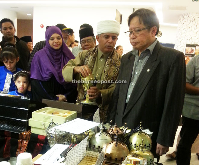 Abang Johari (right) listens to an explanation from Helmi (second right) while visiting a booth at the Yemen Festival.