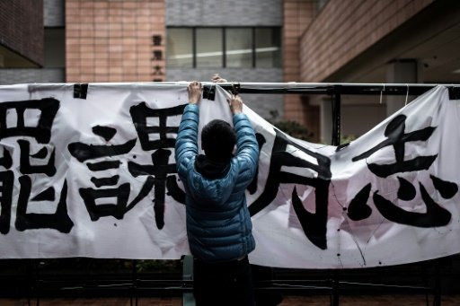 A student sets up a banner during a rally at Hong Kong University on January 20, 2015 protesting against the appointment of Arthur Li, known to be close with the government, as chairman of the university's governing council last month. - AFP Photo