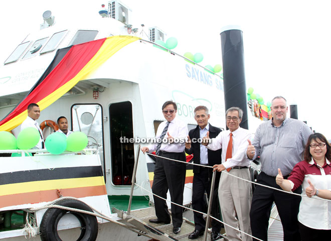Abang Johari (left) gives the thumb-up before boarding the Sayang Sarawak to try out its river cruise, while van Piggelen stands at second right. — Photo by Chimon Upon