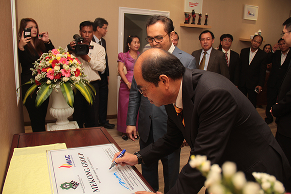 Entri signs the plaque at the joint launching of the Mekong Group with Vongsey in Phnom Penh.