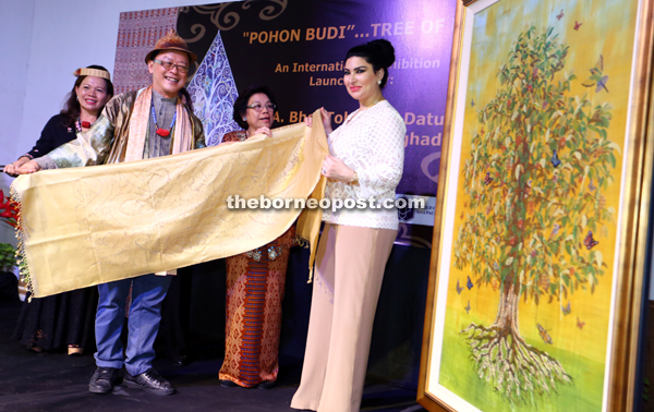 Ong (left) presenting a shawl to Raghad as a souvenir after she launched the Tree of Life exhibition while Tourism Assistant Minister Datuk Gramong Juna's wife Datin Catherine Gramong (centre) looks on. — Photos by Muhammad Rais Sanusi