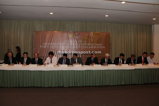Ting Chung (sixth left) and others sign the MOUs, as Len (sixth right) looks on.