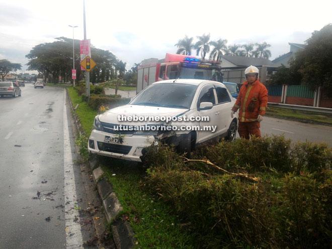 TERBABAS: Kelihatan anggota bomba sedang melihat keadaan kereta Saga yang terbabas di Jalan Wan Alwi.