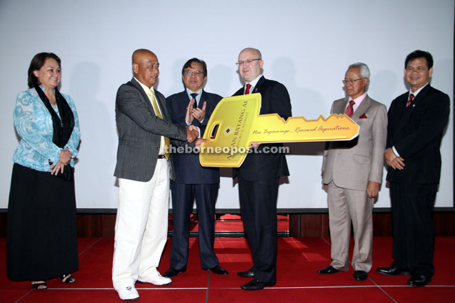 Warmington (third right) hands over a mock key to Samat witnessed by Abang Johari (third left). Gracie is at left. — Photo by Chimon Upon