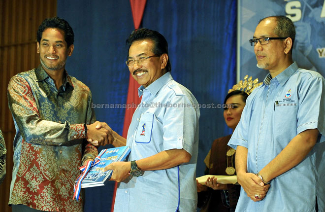 Khairy (left) hands over the Indeks Belia 2015 book to Musa while Tawfiq (right) looks on. — Bernama photo