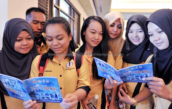 Trainees from Kota Kinabalu Tailoring Club browsing through the Indeks Belia 2015 book. — Bernama photo