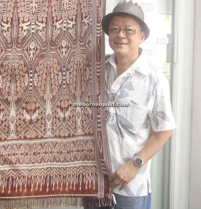Co-curator Edric Ong with a contemporary silk pua kumbu ikat textile 'Tiang Ranyai Tree of Life' by master weaver Bangie Embol.