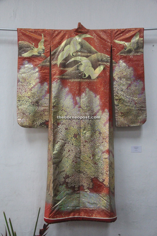 An elaborate Japanese wedding garment called a uchikake auspiciously decorated with a sakura tree in bloom and cranes in flight. This was worn by the bride.