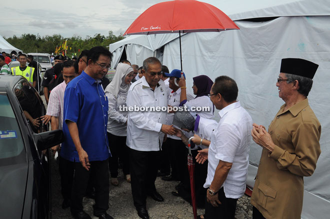 Adenan being welcomed upon arrival at the launching of Kemuyang development project, while Abdul Karim (left) looks on.