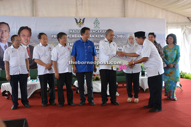 Adenan (fifth left) symbolically hands over TOL to Penghulu Abang Ahmad from Kampung Hilir while (from second left) Wong, Dr Annuar, Abdul Karim, Jamilah and others look on.