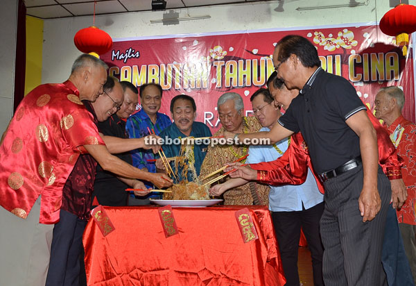 Manyin (sixth left) and several members of Serian Rando/Maksak toss vermicelli noodles to wish for prosperity and good fortune.