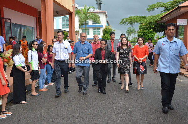 Dr Yeoh (centre) accompanies Riot (second left) upon the latter's arrival for the event. Lau is at fourth left.
