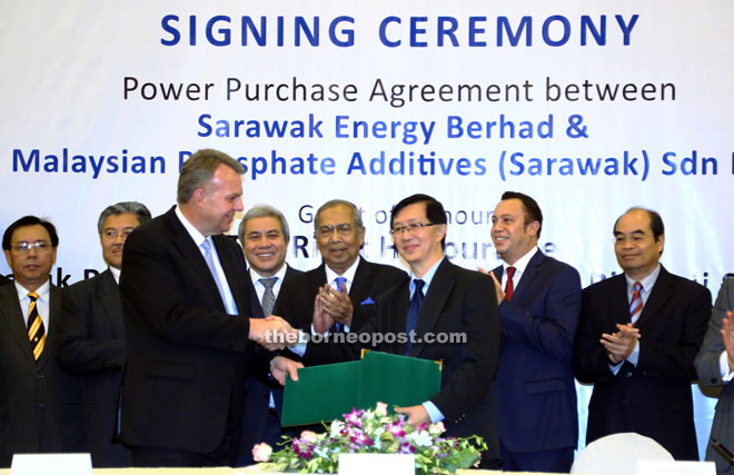 Adenan applauds the power purchase agreement between Sarawak Energy and Malaysian Phosphate Additives as Sjotveit (left) exchanges documents with Lim. — Photo by Muhammad Rais Sanusi