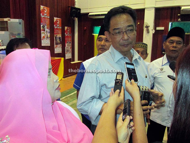Abdul Karim being surrounded by reporters after the handover at SMK Hajah Laila Taib. On his right is Rubiah. — Photo by Jeffery Mostapa