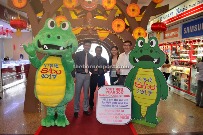 Wong (left) and others giving the thumbs-up to the mascot-naming competition promotional placards at the main entrance of Wisma Sanyan.