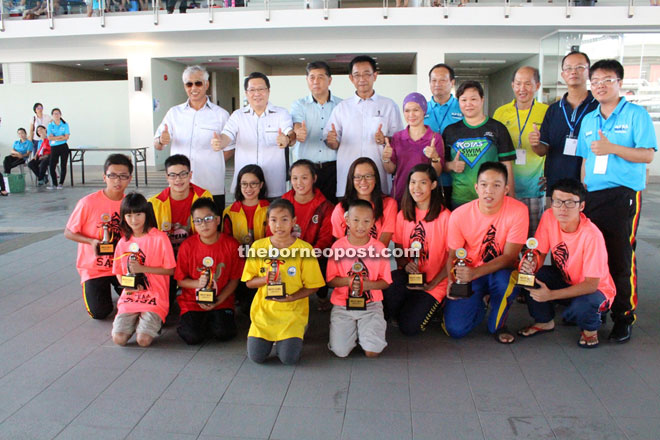 The best boy and best girl swimmers posing with (from left) Wahab, Wee, Sarawak Sports Corporation CEO Dr Ong Kong Swee, Karim, organising chairman Anthony Kong (fifth right) and team managers after the awards presentation.