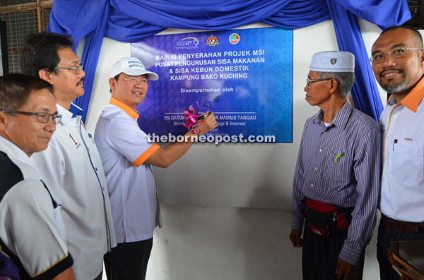 Madius signs the commemorative plaque to officiate at the handover of the MSI project to Kampung Bako Compost Centre.