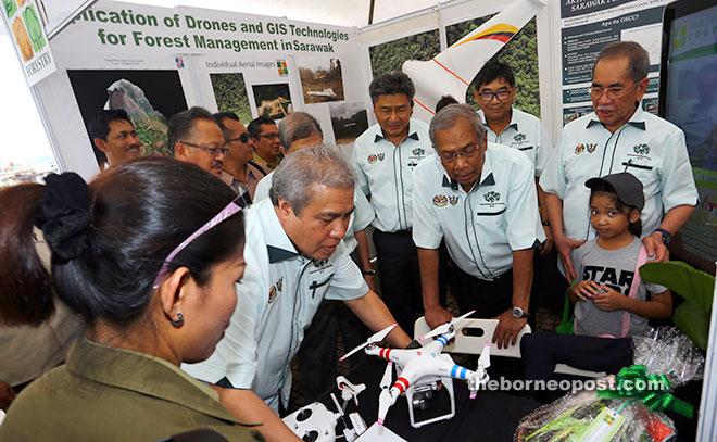 Adenan (second right) and Awang Tengah (second left) take a closer look at a drone technology. Wan Junaidi is at right. —Photo by Muhammad Rais Sanusi
