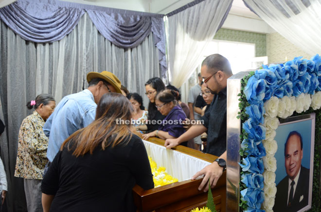 Dr Patau's family members pay their last respects to him. Also seen is Sean (right), and his second right, Teresita.