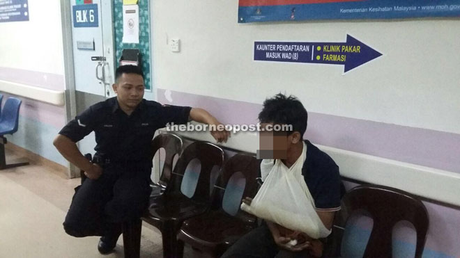 A policeman keeps watch over the suspect at the hospital.