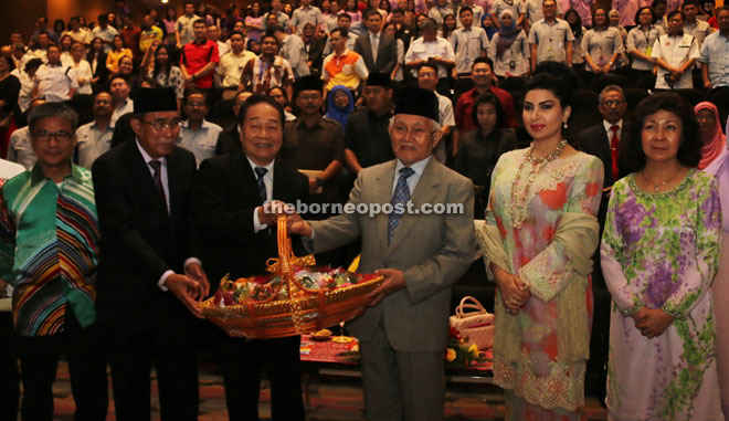 Wong (third from left) presents a memento to Taib while (from left) Dr Annuar, Len Talif, Raghad, Leong and others look on.