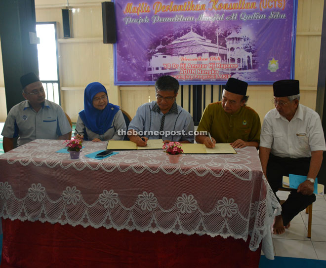 Dr Annuar (centre) signs the MoU on behalf of Lakis, and Azizah on behalf of UCTS.