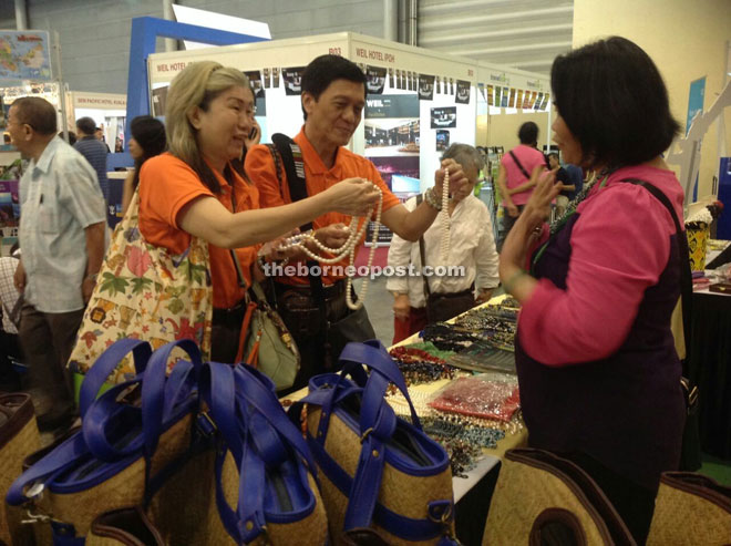 Singaporean visitors are fascinated by local Sarawak beads at the fair.