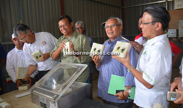 Ahmad Shabery (third right) and Jabu (second right) holding packets of processed Bario rice at Bario Ceria Sdn Bhd.