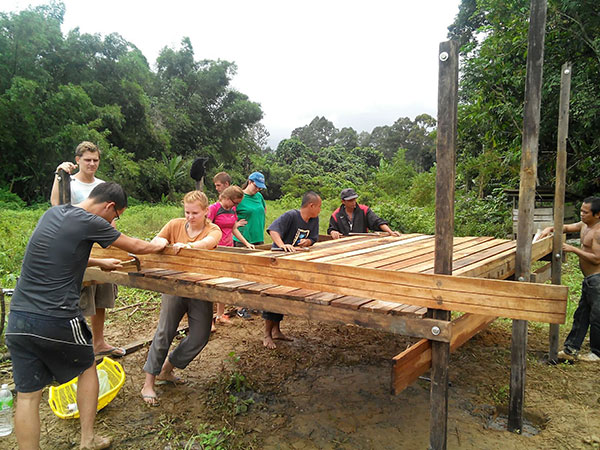 Foreign and local volunteers constructing a house for a disadvantaged family.