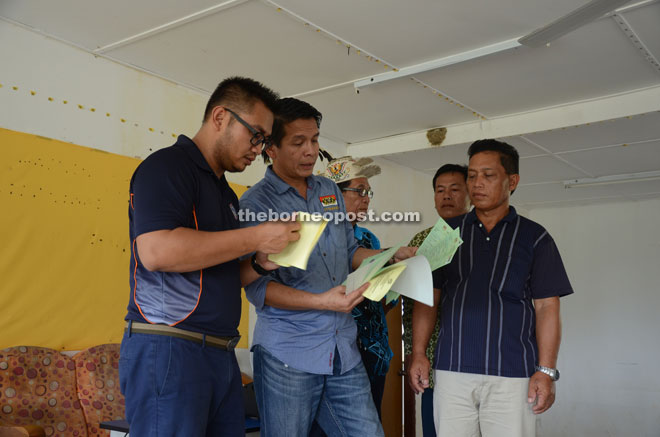 Affrizan (left) and Dennis verify the documents before handing them over to the applicants.