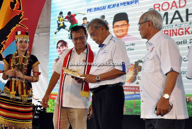 Adenan (second right) looking at a memento given to him by Ahmad Shabery (second left) in conjunction with the launch of Road to Maha 2016 while Jabu (right) looks on.