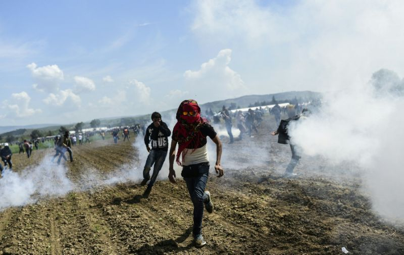 Refugees and migrants flee the tear gas as they clash with Macedonian police during a protest to reopen the border near their makeshift camp in the northern Greek border village of Idomeni, on April 10, 2016 (AFP Photo/Bulent Kilic)