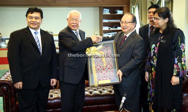 Manyin (second left) presents Dompok with a memento of pua kumbu. — Photo by Muhamad Rais Sanusi