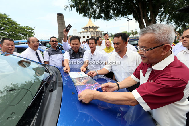 Talib (right) places the promotional sticker on one of the taxis while being assisted by Sarawak Tourism Board chief executive officer Datu Ik Pahon (fourth left).