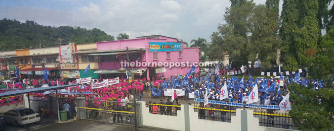 BN supporters (in blue) and Nyomek's supporters (in pink) gather in front of the nomination centre at Bau District Council.
