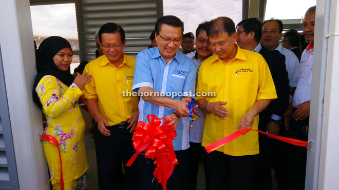 Liow cutting the ribbon to declare open the Miri Airport's new covered walkway and apron, witnessed by Lee (second left) and Ting (right).