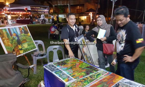 Local batik painter Noel Beluluk (left) entertaining customers at his stall.