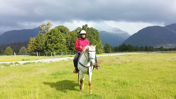 Aliya tries out horse riding during a free day.