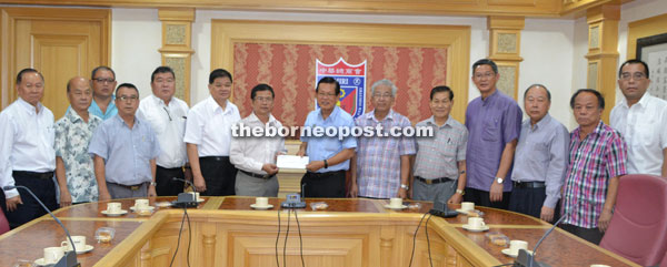Kim Shin (seventh right) hands over the proposal letter for AirAsia to Khoi Yun at the MCCCI meeting.