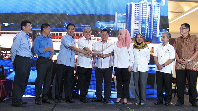Tengah (fourth left), Julaihi (third left) together with Che Nazli (fourth right) touches the screen of a tablet to symbolise the launch of the state-level 'SMEs Week 2016'. Also seen on the stage (from right) Abdul Aziz, Paulus and Rosey, while from left Liaw and Ripin.