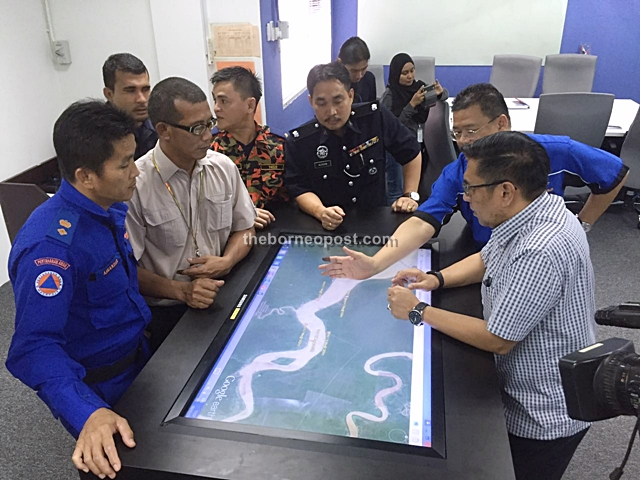 Azharuddin (right) and representatives of other agencies going over a map of the crash site.