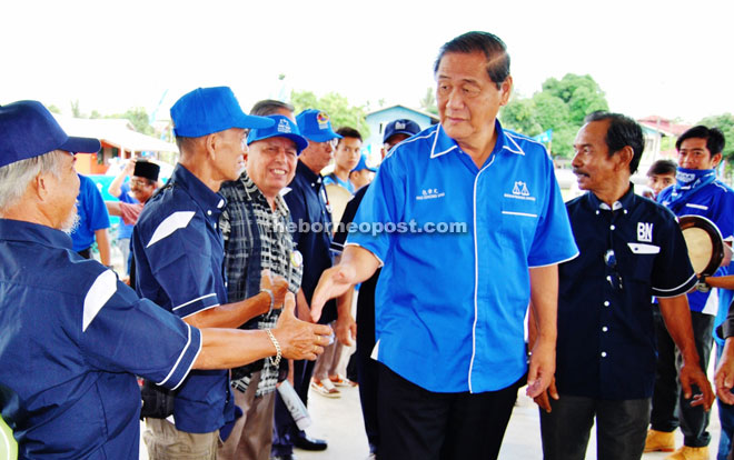 Pau shakes hands with locals upon arriving at the community hall for the gathering
