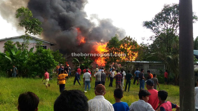 Neighbours gathering at the scene of the fire in Kampung Tupong Batu.
