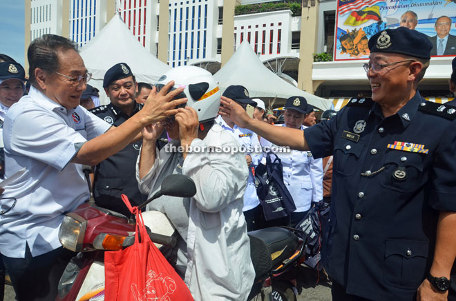 Wong (left) helps a motorcyclist to put on the safety helmet as Mazlan (second left) and Koo (right) look on.